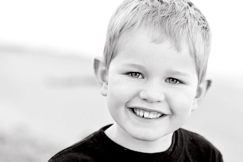 a black and white photo of a boy smiling captured by Tauranga children and family photographer Susanna