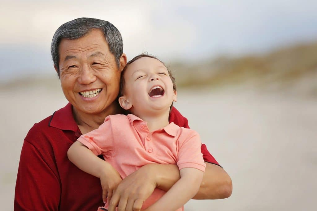 a portrait of grand dad holding his grandson and laugh on Papamoa Beach captured by Tauranga children and family photographer Susanna