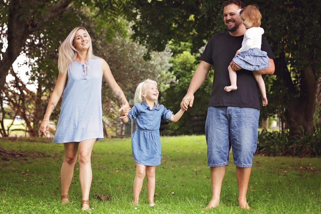 family holding hands and laughing captured by Tauranga children and family photographer Susanna