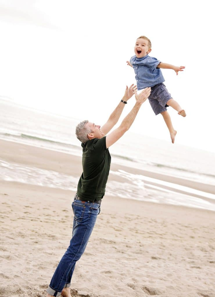 a photo of father throwing his son up on the beachcaptured by Tauranga children and family photographer Susanna
