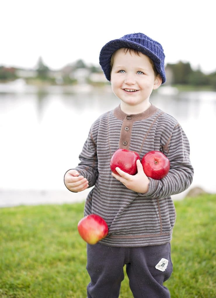 children portrait, a little boy holding some apples on the river bankcaptured by Tauranga children and family photographer Susanna